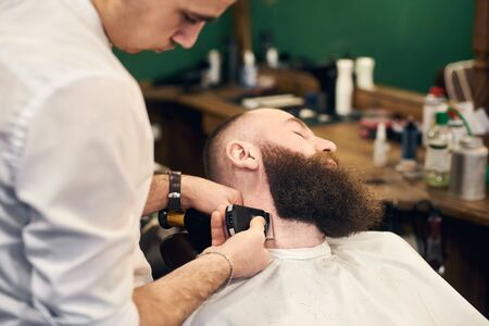 Bearded man client in hairdresser chair throwing back his head during barber styling clients beard with shaver machine. Professional tools, accessories and care products on blurred background. Reklamní fotografie