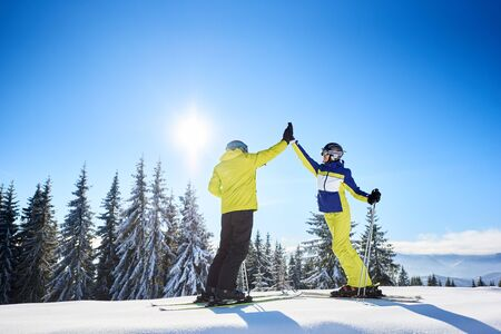 Young couple man and woman giving high five to each other under sunny blue sky high in mountains. Skiers after successful skiing up to mountain top. Coniferous forest on background.