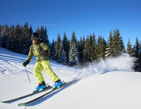 Young sporty man skiing up and down slopes. Male skier training and having fun in sunny winter day. Backcountry skiing concept. Fir trees and clear blue sky with copy space on background.