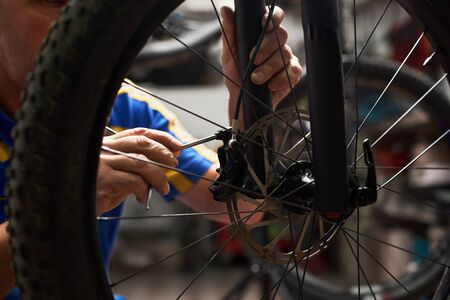 Cropped shot of male serviceman working in bicycle repair shop, mechanic repairing bike brakes using special tool, wearing protective workwear