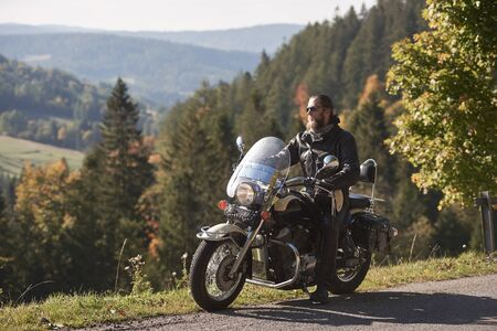 Handsome bearded biker in black leather jacket and sunglasses sitting on modern motorcycle on country roadside, on blurred background of foggy green hills covered with dense spruce forest.