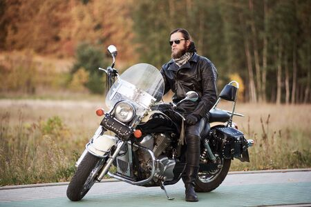 Young bearded biker in black leather clothing and sunglasses sitting on cruiser motorcycle on clean paved roadside on background of vintage trees golden bokeh foliage. Reklamní fotografie