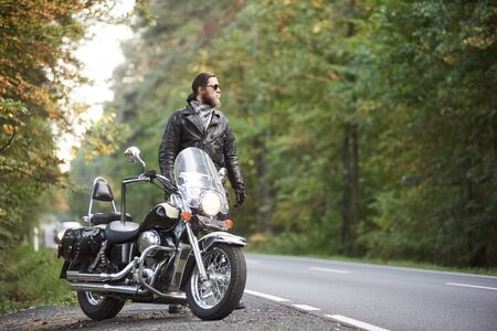 Young bearded tall athletic motorcyclist in dark sunglasses, black leather jacket and gloves standing at shiny modern powerful motorbike on blurred background of hilly asphalt road and green trees.