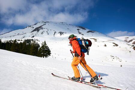 Skitourenmann, der am sonnigen Tag die Spitze in schneebedeckten Bergen erreicht. Schnee- und Winteraktivitäten, Skitouren in den Bergen.