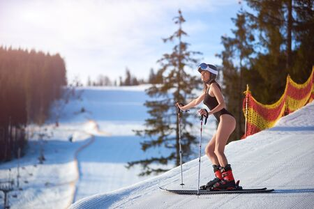 Sexy attractive young woman in black swimsuit, helmet and goggles standing on skis on steep hill track on background of mountain landscape on sunny winter day. Extreme sports and recreation concept. Standard-Bild