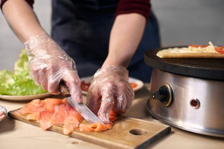 Focus on process of slicing with knife pieces of fish on cutting board for cooking food. Cooks hands in disposable gloves preparing components for dish. Equipment, ingredients on blurred background.