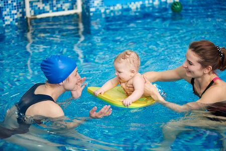 Adorable baby enjoying swimming on floating board in pool with his mother and trainer helping. Side view. Interesting game and useful pastime for children. Newborn baby at sportive active family