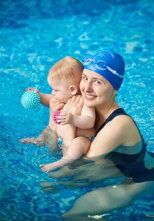 Young mother with baby in swimming pool. Happy smiling woman looking in camera while having fun and swimming time with her newborn child playing in blue water. Horizontal portrait snapshot