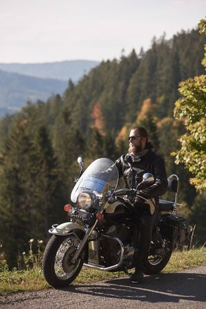 Handsome bearded biker in black leather jacket and sunglasses resting on cruiser motorcycle on country roadside, on blurred background of foggy green hills covered with dense spruce forest. Banco de Imagens