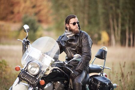 Young bearded motorcyclist in black leather clothing and dark sunglasses sitting on black shiny modern motorbike, on blurred vintage sunny bokeh background of golden-green trees foliage on sunny day. Banco de Imagens