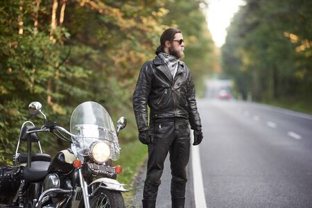 Profile bearded athletic long-haired motorcyclist in black leather outfit and dark sunglasses standing at shiny cruiser powerful motorbike, on blurred background of hilly asphalt road and green trees. Banco de Imagens