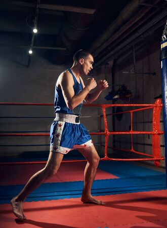 muscular sportsman kick boxer training hard boxing and preparing for fight, kicking and punching heavy boxing bag near the ring at the sport club