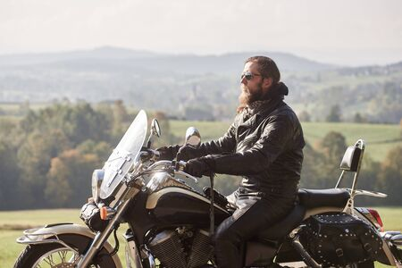 Side view of handsome bearded biker with long hair in black leather jacket and sunglasses sitting on cruiser motorcycle, on blurred background of green peaceful rural landscape and light foggy sky.