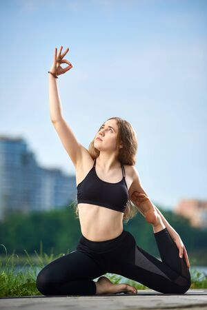 Fit girl with beautiful long hair doing yoga in sportswear under morning blue sky against residential city view, wearing black top and pants, meditation, zen