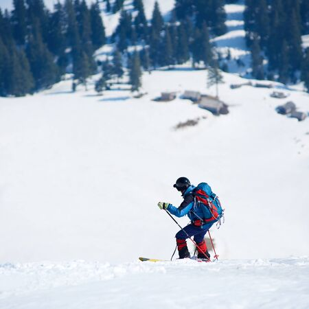 Skier hiker with backpack on skis in deep white snow on background of beautiful winter landscape, wooden huts on mountain valley and green spruce trees. Tourism, ecological holidays concept. Banco de Imagens