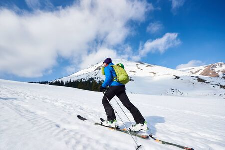 Skier tourist with backpack touring on skis in deep snow uphill on background of bright blue sky and beautiful mountain panorama. Winter vacations, active lifestyle, skiing and trekking concept.