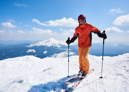 Smiling sportsman skier in helmet and goggles standing on skis holding ski poles in deep white snow on copy space background of bright blue sky and highland landscape. Winter skiing hobby concept. Banco de Imagens