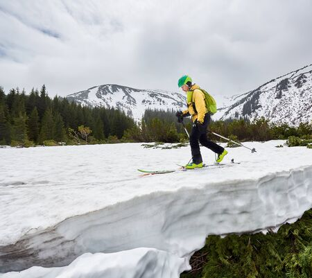 Snow-covered mountain and off-piste skier. Side view of cross country skier man in green helmet walking on ski along green coniferous forest at foot of mountain. Active healthy lifestyle