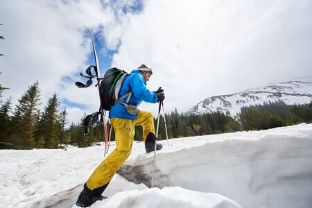 Side view of man snowboarder in bright ski suit climbing on snow-covered foothill using ski-tour equipment. Ski touring in wooded mountains. Low angle snapshot. White sky on background with copy space