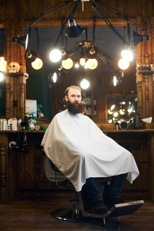 Full length portrait of bearded man overgrown sitting in retro chair before haircutting in modern barber shop. Big mirror at professional equipped workplace illuminated by many lamps