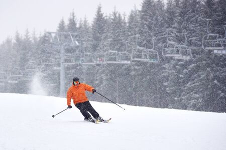 Young proficient man skiing on ski run slope during heavy snowfall. Chairlift and fir forest on background. Monochrome view. Recreational outdoors sports vacation and healthy leisure on solitude