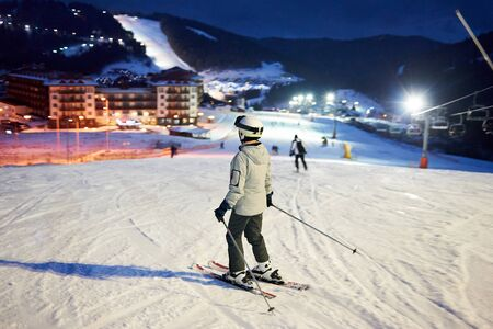 Back view of female skier after skiing day standing on skis, looking on wonderful ski resort lighted by lanterns and enjoying with fascinating views in darkness. Mountains views on blurred background. Banco de Imagens