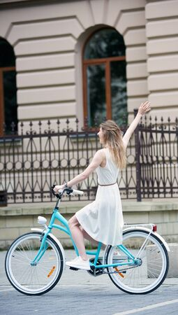 Young woman in light white dress and white sneakers is riding a blue bike on the street in the city with one hand up, full length, beautiful building with fence on background, side view