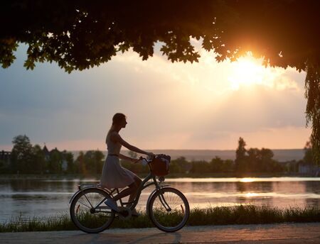 Happy woman riding a retro bike with a basket on the road near the lake on a sunset. Girl enjoying the magical view of the suns rays of the falling sun at the end of the day Banco de Imagens