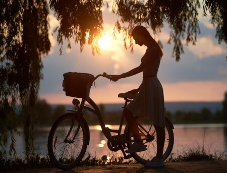 Silhouette of a romantic young girl with a bicycle near urban lake at amazing summer sunset, willow branches on the foreground Banco de Imagens
