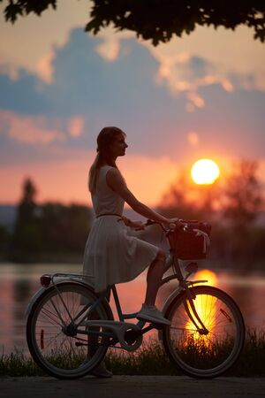 Romantic girl with a bike keeping her foot on a pedal is watching purple sunset at the lake, all colors of the sky, orange sun path, side view