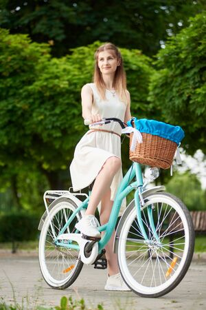 Young girl in white dress and sneakers is sitting on her blue citybike with a basket, looking away, vivid green trees on the background, full length