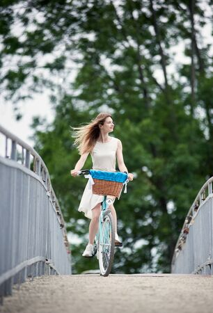 Young girl in a white summer dress is riding her blue citybike on the bridge, blurred trees on background, enjoying windy weather