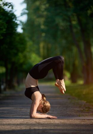 Strong, young girl doing a forearm stand in the park alley with green trees in the summer. Practicing Vrischikasana, Scorpion exercise, full length, balancing
