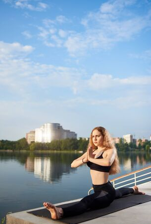 Young woman practicing yoga on urban lake, wearing black top and pants. Relax in nature under blue sky. Sitting on the twine. Meditation. Residential background. Copy space