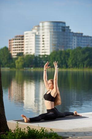 Relaxed girl with long hair sits in a longitudinal twine on yoga mat and raised her hands up near the lake against blurred background of buildings. Morning yoga training outdoor all day energy boost