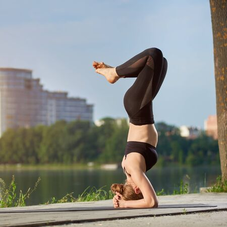 Young woman practicing yoga at city lake. Doing Salamba Sirsasana, supported headstand pose. Leading a healthy lifestyle outdoor, meditation in nature Stock Photo - 135467910