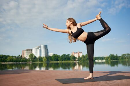 Attractive girl in a black sports suit standing in pose of king of dance, Asan Natarajasana, in the background of city landscape with the lake and trees. Girl forms beautiful posture under blue sky