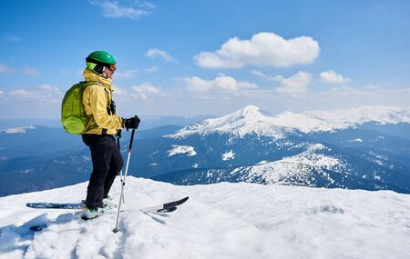 Esquiador deportista en casco y gafas con mochila de pie de perfil sobre esquís sosteniendo bastones de esquí en nieve blanca profunda, sobre fondo de espacio de copia de cielo azul brillante disfrutando de hermosas vistas a la montaña.