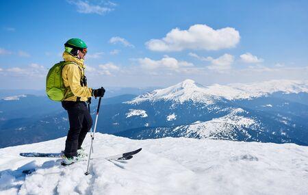 Sportler Skifahrer in Helm und Brille mit Rucksack im Profil auf Skiern mit Skistöcken in tiefweißem Schnee, auf Kopienraum Hintergrund des strahlend blauen Himmels mit schönem Bergblick.