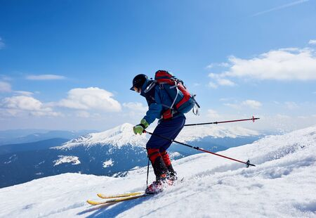 Sportsman skier in bright clothing, helmet and goggles with backpack riding down steep snowy slope on copy space background of blue sky and mountain landscape. Winter holidays, extreme sport concept. Banco de Imagens