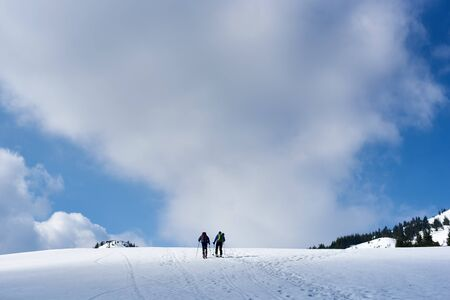Back view of two hikers on horizon, skiers with backpacks trekking on skis up snowy mountain hill on copy space background of bright blue sky on frosty sunny day. Winter active vacations concept.