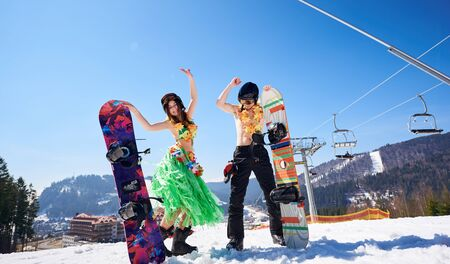 Happy attractive snowboarders in flower garlands, young woman in boots, bra and skirt and bearded man with bare torso dancing with snowboards on background of blue sky, winter mountains and ski lift. Banco de Imagens