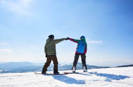 Back view of two happy tourists snowboarders on mountain summit on copy space background of blue sky and woody mountains on sunny winter day. Extreme winter sports, active lifestyle concept.