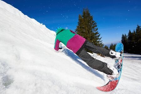 Snowboarder dangerously riding snowboard on snowy steep mountain slope on background of blue sky and spruce trees on sunny winter day. Winter sports and recreation, outdoors activities concept. Banco de Imagens
