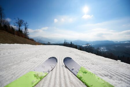 Close-up of pairs of skis on white snowy ski track, beautiful winter mountain landscape at dawn or evening and blue sky copy space background. Sports and recreation, active lifestyle concept.