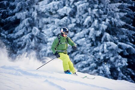 Proficient skier coming down along wooded hillside using professional ski equipment and making deep snow powder. Winter outdoors activities concept. Picturesque forest scenery on background. Side view