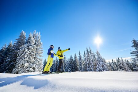 General view of happy family after skiing on sunny day. Man and woman on skis in goggles stopping on slope for looking at mountain landscape. Man showing thumbs up. Low angle snapshot with copy space. Stok Fotoğraf