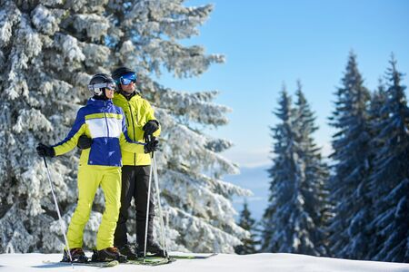 Happy couple embracing and enjoying mountain views and scenery on winter sunlight. Family vacation, winter activities, ski resort concept. Picturesque snowy firs, blue sky on background. Copy space. Stok Fotoğraf