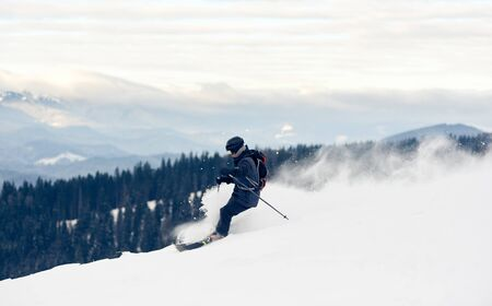 Panoramic photo with skier, winter mountains view. Young man skiing downhill from snow-capped mountain top. Risk, overcoming obstacles, hardiness, victory, achievement concept. Grey sky on background. Stok Fotoğraf