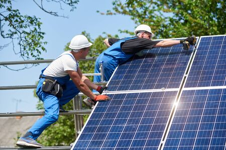 Two young technicians mounting with screwdriver heavy solar photo voltaic panel on tall steel platform on green tree background. Exterior solar panel voltaic system installation, dangerous job concept